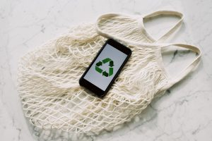phone screen with recycle icon on white eco friendly net bag