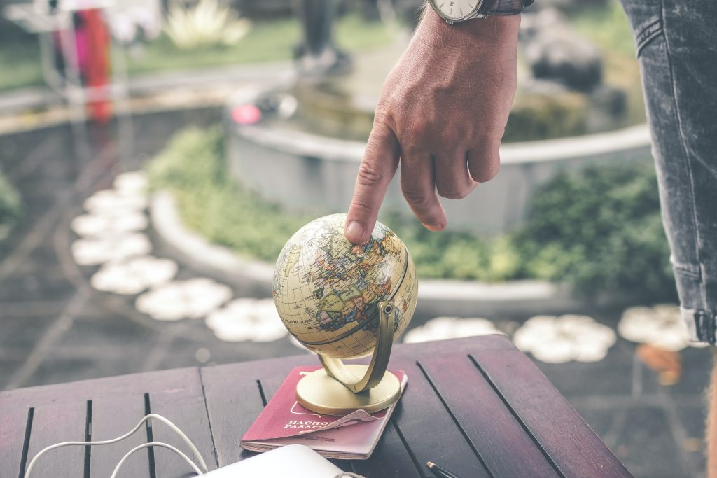 finger pointing at small globe