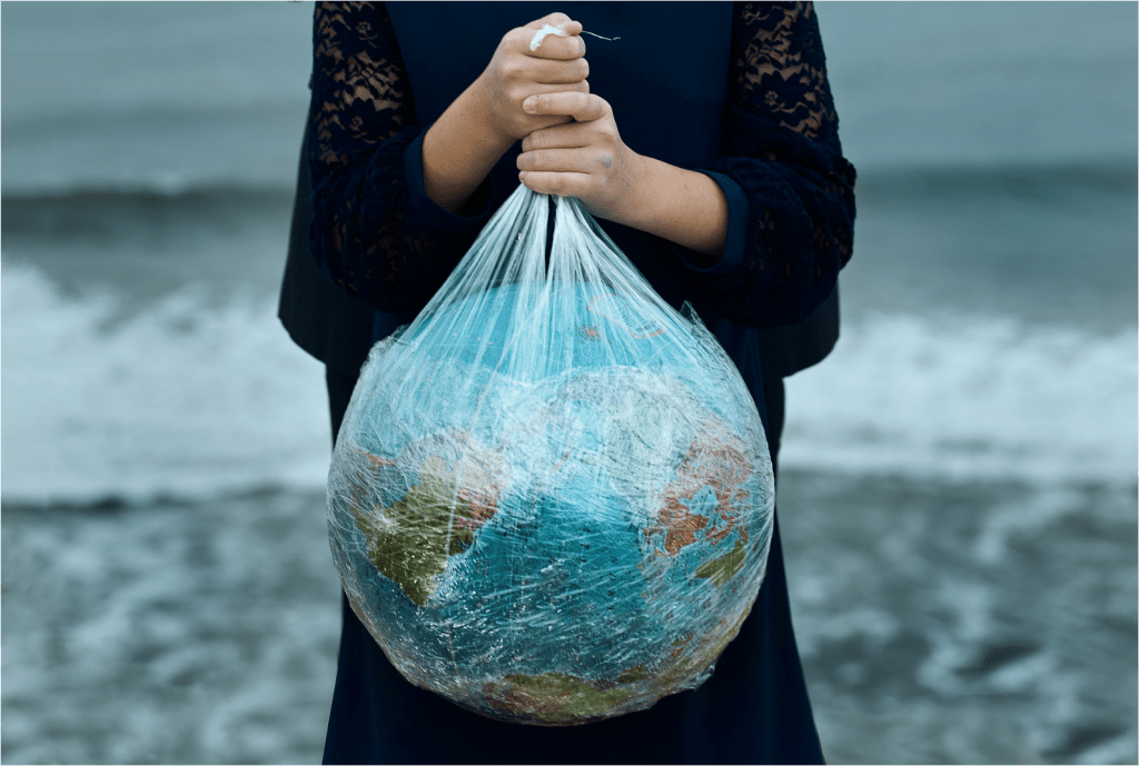 woman holding plastic wrapping around the globe